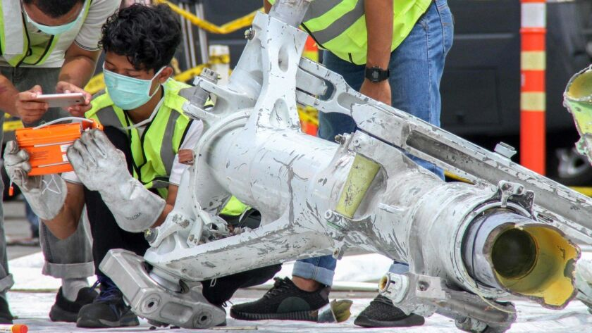 Lion Air investigators examine part of the landing gear of the ill-fated Lion Air flight JT 610 at the port in northern Jakarta on Nov. 5.