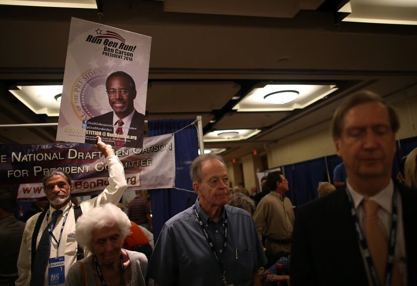 An attendee holds a sign in support of a presidential run by retired neurosurgeon and columnist Ben Carson during the 2014 Republican Leadership Conference in New Orleans, La.