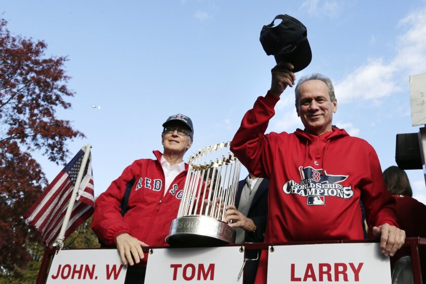 Boston Red Sox president Larry Lucchino, right, tips his cap to fans as majority owner John Henry holds the 2013 World Series championship trophy during a parade in celebration of the team's 2013 title. (AP Photo/Charles Krupa)