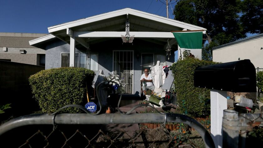 Michael Alva, 53, sits with his oxygen tank outside his home in a neighborhood in Paramount.