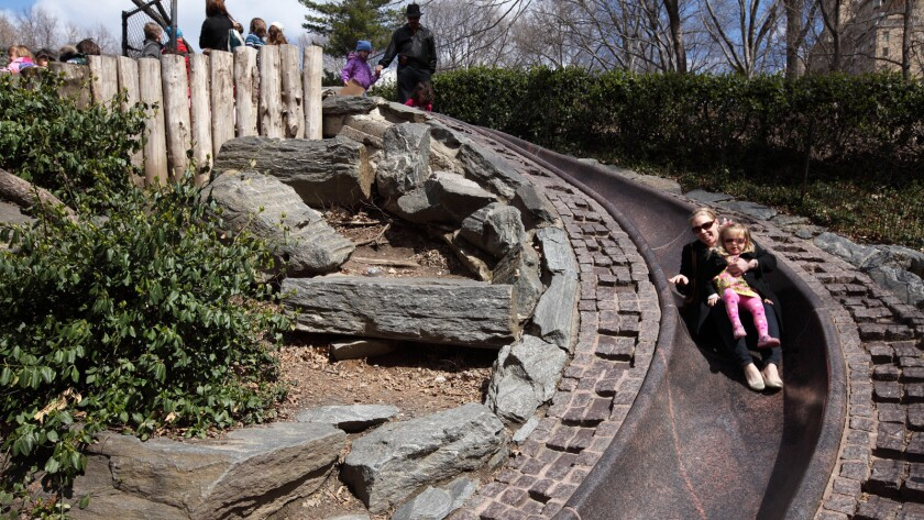 Girl and mother sliding down slide in Billy Johnson Playground in Central Park.