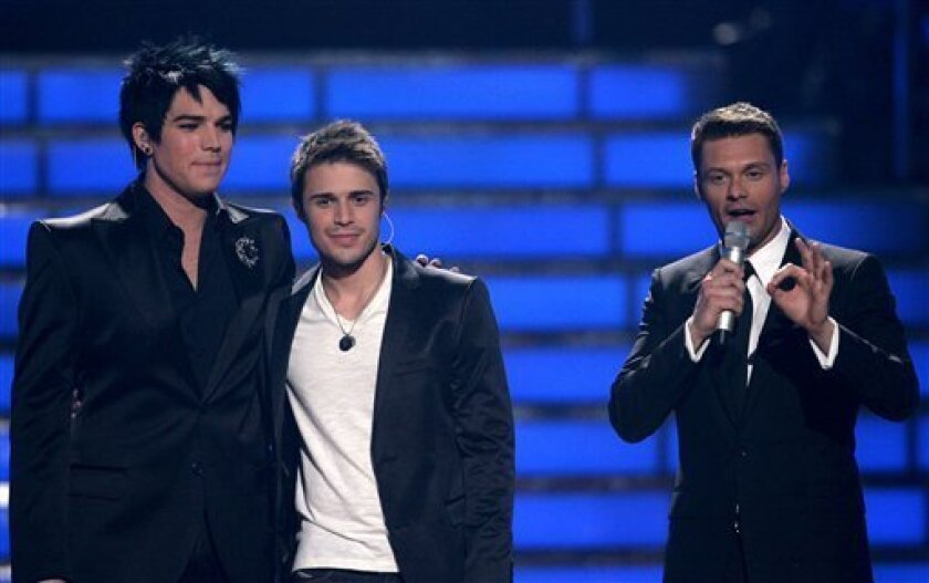 FILE - In this May 20, 2009 file photo originally released by Fox, finalists Adam Lambert, left, Kris Allen, center, and host Ryan Seacrest are seen during the season finale of American Idol in Los Angeles. (AP Photo/Fox, Evans Vestal Ward)