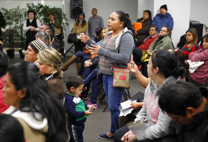 Rosa Robles asks about eligibility to stay in the U.S. as her son Alan Gomez, 3, stands near her at a workshop on applying for deferment from deportation in McAllen, Texas.