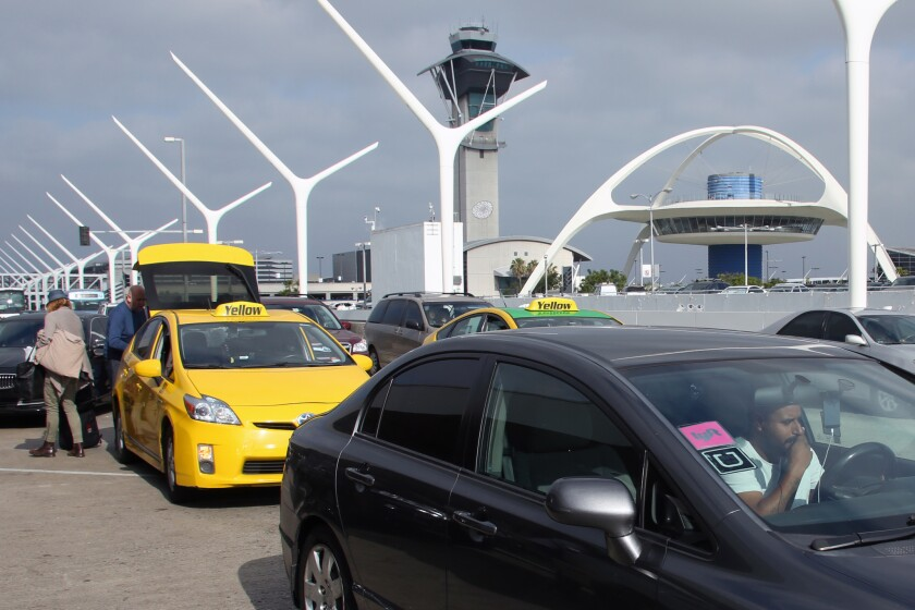 A car with Uber and Lyft stickers leaves the departures area of LAX, with taxis behind it, last month.