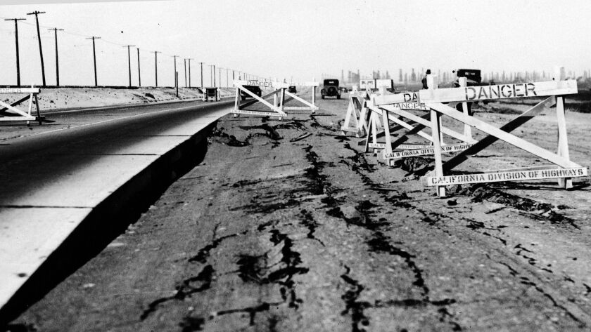 Cracks are seen in a Long Beach roadway after a massive earthquake struck March 10, 1933. An oil field is visible in the background at right.