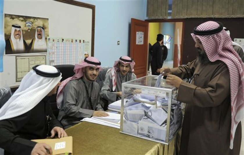 A Kuwaiti citizen casts his vote at a polling station in Salwa, Kuwait City on Thursday, Feb. 2, 2012. Officials said 400,296 Kuwaitis are registered to vote in the first parliamentary election since May 2009. The more than 280 candidates include 23 women, including re-election bids by four lawmakers who were the first women in the assembly. (AP Photo/Gustavo Ferrari)