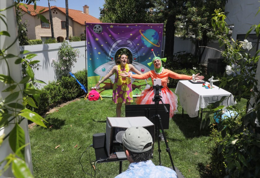 """On Sunday Ruth Weber, right, and her daughter Emilia Lopez-Yañez perform their kid's show """"Sunday Funday"""" live on the internet in Ruth's backyard. Below operating the computer and camera is Ruth's husband John Weber."""