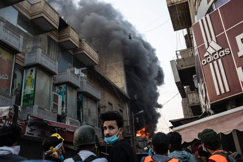 A building is set ablaze near Ahrar Bridge, where there have been recent clashes between demonstrators and Iraq security forces, Sunday in Baghdad. Thousands of demonstrators have occupied central Baghdad since Oct. 1, calling for government and policy reform.