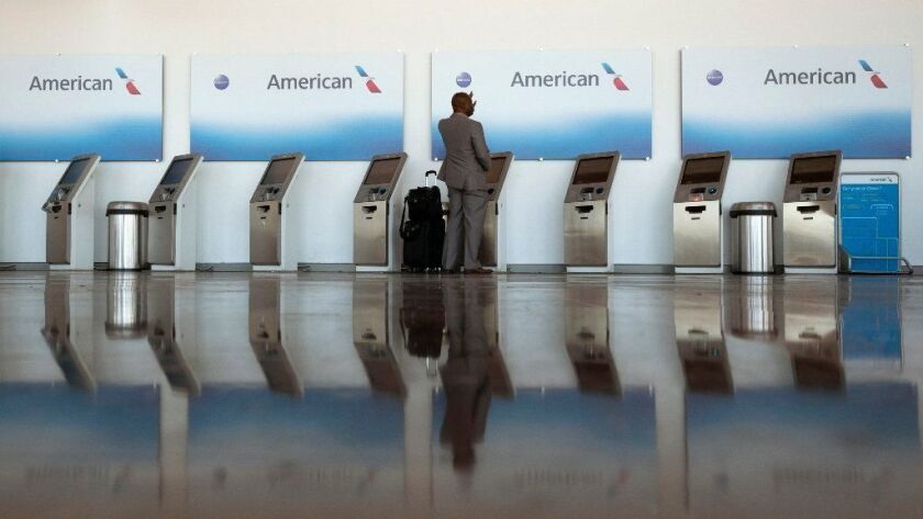 a traveler waves for assistance Nov. 21, 2018, as he checks in at an American Airlines kiosk at Washington Reagan National Airport in Arlington, Va. American Airlines said March 15, 2019, that it is stopping flights to Venezuela.