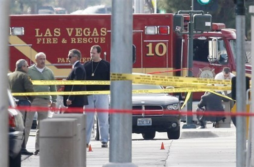 Law enforcement officials investigate a shooting at the Lloyd D. George federal courthouse building in downtown Las Vegas Monday, Jan. 4, 2010 in Las Vegas. A court security officer and the suspect were killed. A U.S. marshal was wounded. (AP Photo/Isaac Brekken)