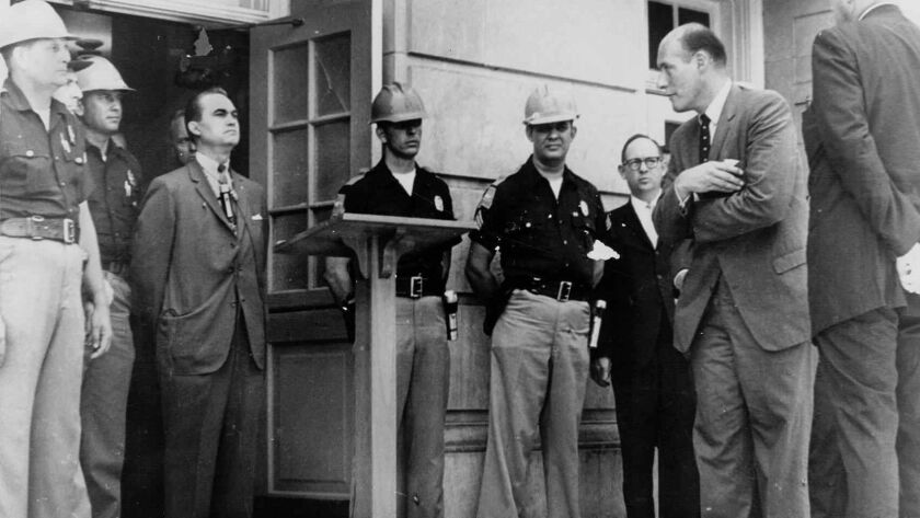 Then Alabama Gov. George Wallace, wearing suit at left, is shown on June 11, 1963, standing at the door of Foster Auditorium in Tuscaloosa, Ala., as he tries to block the admission of two black students to the then- all-white University of Alabama.