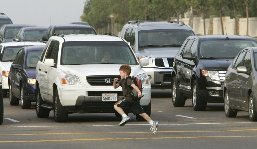 A child ran across the crosswalk at Ted Williams Parkway and Shoal Creek Road. Federal stimulus money will help build a pedestrian bridge at the dangerous crossing. Parents say many drivers fail to slow down in the school zone. (Charlie Neuman / Union-Tribune)
