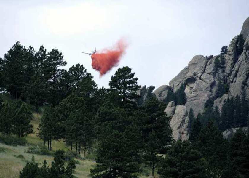 A tanker drops fire retardant near Bear Peak while battling a blaze near Boulder, Colo.