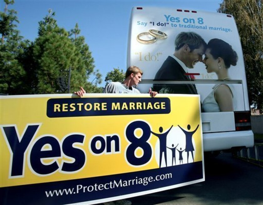 In this file photo from Oct. 20, 2008, Richie Beanan, from Los Angeles, puts a sign on a bus that will tour California in support of Proposition 8 after a rally in Sacramento, Calif. California voters passed proposition 8 in November, eliminating the right for same-sex couples to marry. (AP Photo