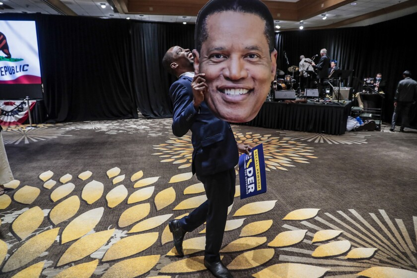 Errol Webber of Costa Mesa carries a cutout picture of Larry Elder at the candidates' election party