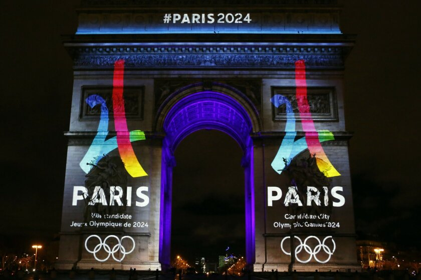 FILE - In this Feb. 9, 2016, file photo, the Eiffel Tower-shaped bid logo for Paris 2024 is unveiled on The Arc de Triomphe on the Champs Elysees in Paris. For some reason, four cities submitted bids this week to host the 2024 Olympics, turning in glitzy presentations filled with all sorts of highf