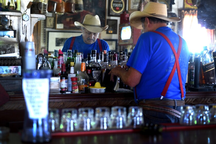 Proprietor Walt Kremin tends to his bar in Gold Point, Nev.