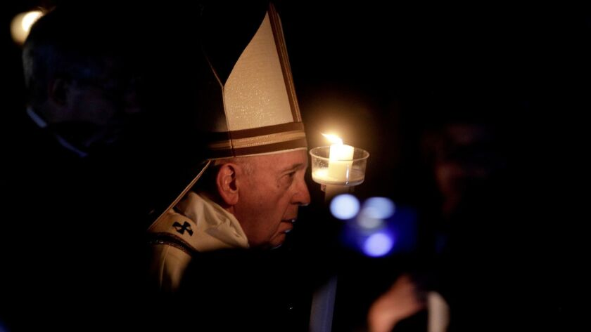 Pope Francis holds a candle as he presides over a solemn Easter vigil ceremony in St. Peter's Basili