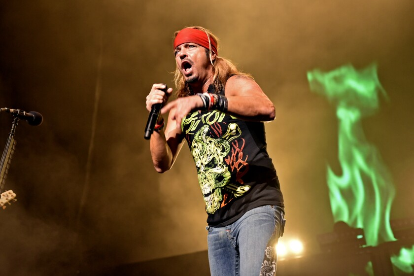 Bret Michaels holds a microphone while performing on stage