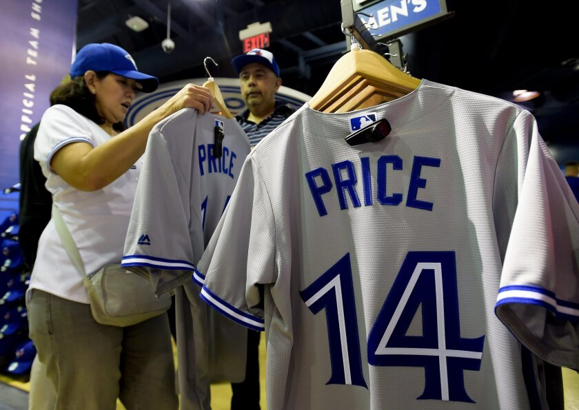 Toronto Blue Jays fans tries on the jersey of newly acquired pitcher David Price before the Blue Jays play the Kansas City Royals during a baseball game, Thursday, July 30, 2015 in Toronto. (Nathan Denette/The Canadian Press via AP) MANDATORY CREDIT