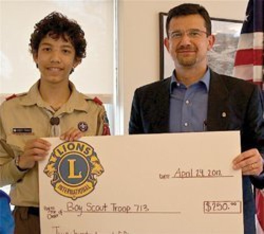 Del Sol Lion President Bulent Erol presents a check to Eagle Scout candidate Robert Francis of Del Mar Boy Scout Troop 713.