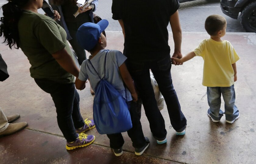 A young boy holds hands with his mother at a bus station in San Antonio after they were released from a family detention center in Texas in July. The group from El Salvador had been held at a family detention center after they were caught entering the country illegally.