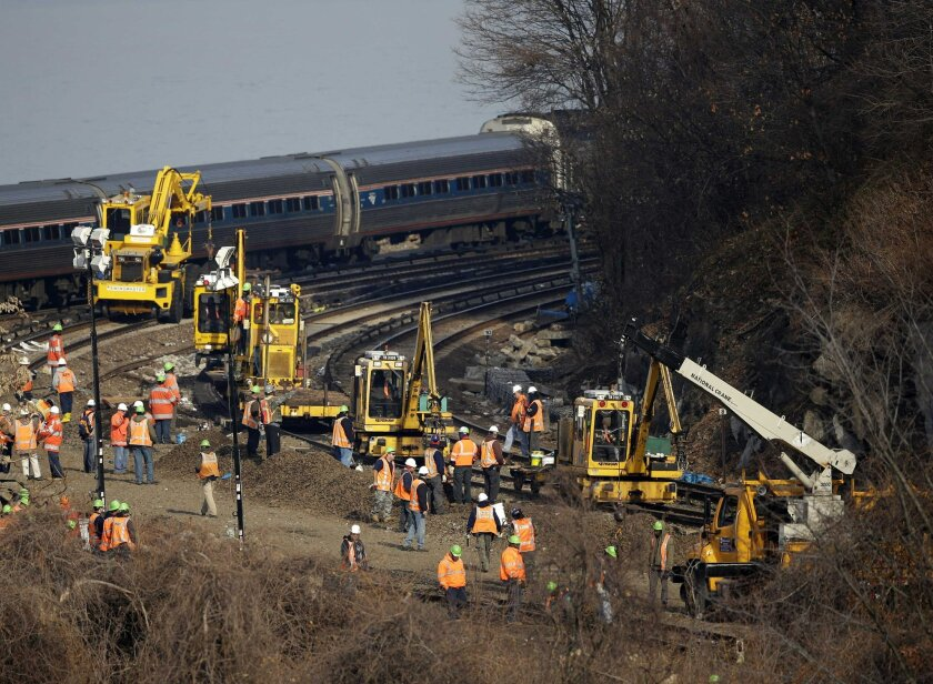 A train passes by the scene of repair efforts at the site of a train derailment in the Bronx borough of New York, Tuesday, Dec. 3, 2013. The National Transportation Safety Board says right now, it doesn't know whether faulty brakes or human error caused Sunday's derailment of a New York City train that killed four people and injured more than 60. But NTSB member Earl Weener says information from the train's two data recorders shows the train was going 82 mph on a turn when it should have been going no more than 30 mph. (AP Photo/Seth Wenig)