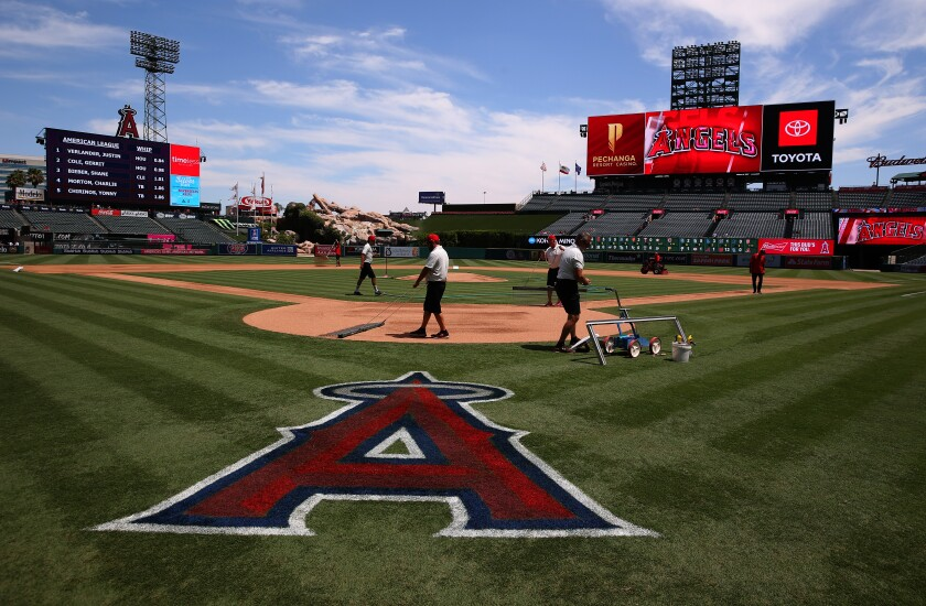 Grounds crews work on the field at Angel Stadium.
