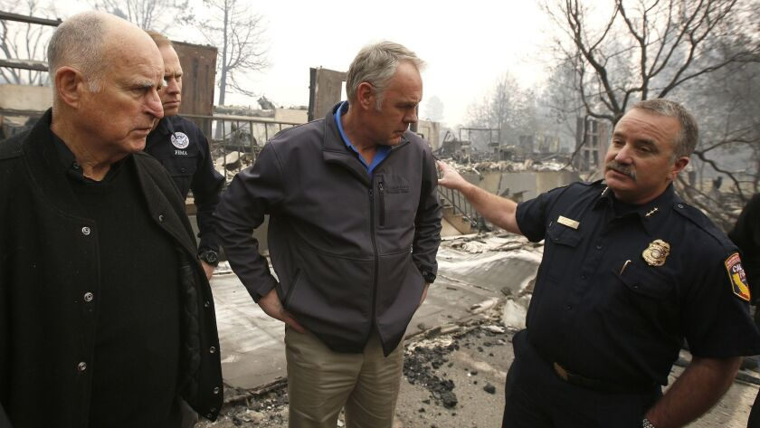 Interior Secretary Ryan Zinke, center, received a briefing from Cal FIRE Regional Chief Scott Upton, right, in fire-stricken Paradise, Calif. Gov. Jerry Brown is at left. But was Zinke listening?