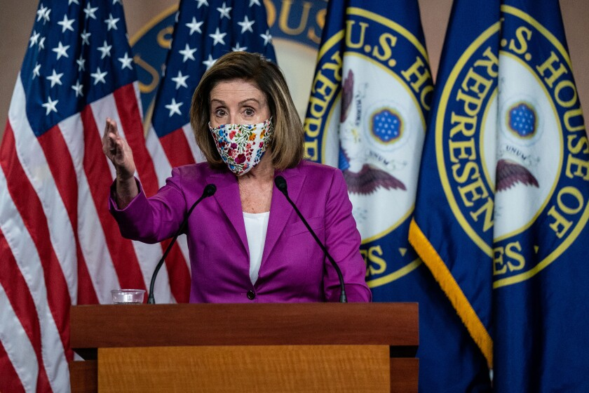 Nancy Pelosi, in mask, gestures as she stands at a podium and speaks into microphones.