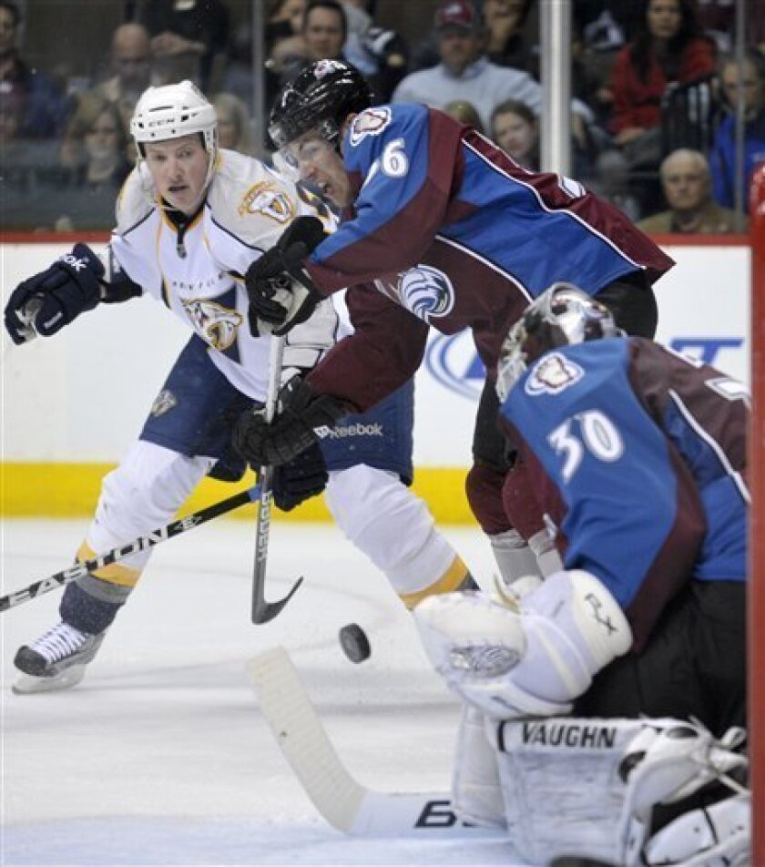 Colorado Avalanche defenseman Jonas Holos, center, of Norway, swats at the puck against Nashville Predators center Jerred Smithson, left, in the first period of their NHL hockey game in Denver on Thursday, March 31, 2011. Avalanche goalie Brian Elliott (30) looks on. (AP Photo/Joe Mahoney)