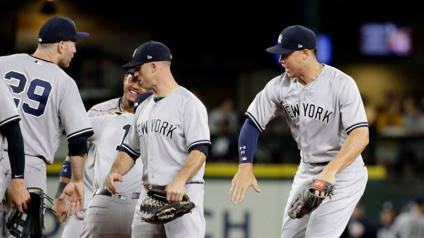 The New York Yankees celebrate their 4-1 win over the Seattle Mariners on Thursday.