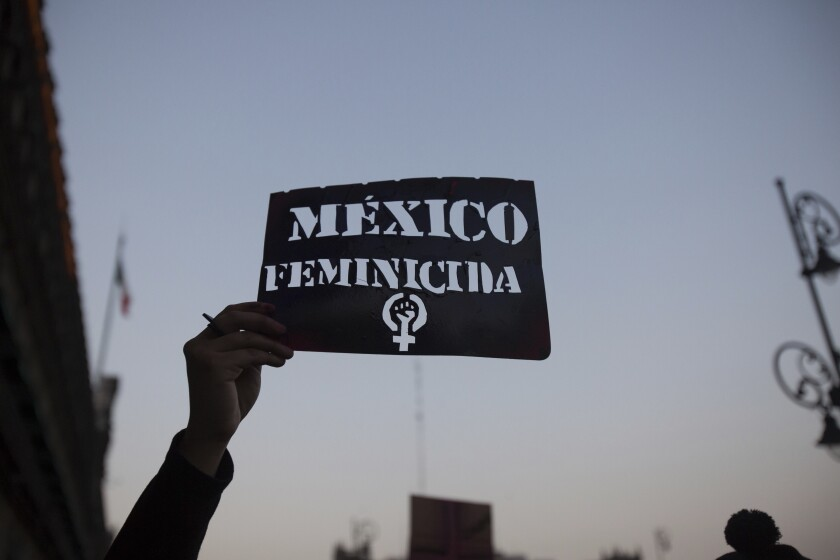 """A demonstrator holds up a stencil of the Spanish message: """"Mexico Femicide"""" in Mexico City, Friday, Feb. 14, 2020. The demonstration against gender violence comes after last week's vicious murder of Ingrid Escamilla by her husband and controversy unleashed by the leaking of images of her body to the press, in a country where an average of 10 women are killed every day. (AP Photo/Ginnette Riquelme)"""