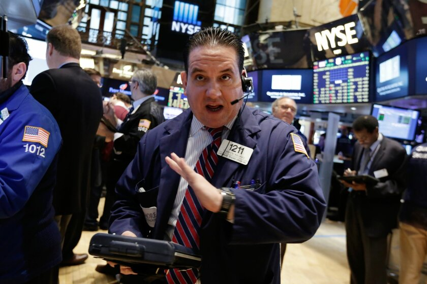 Trader Tommy Kalikas talks on his mobile phone as he works on the floor of the New York Stock Exchange Monday, Feb. 23, 2015. U.S. stocks are opening slightly lower, pulling the market back from an all-time high reached last week. (AP Photo/Richard Drew)