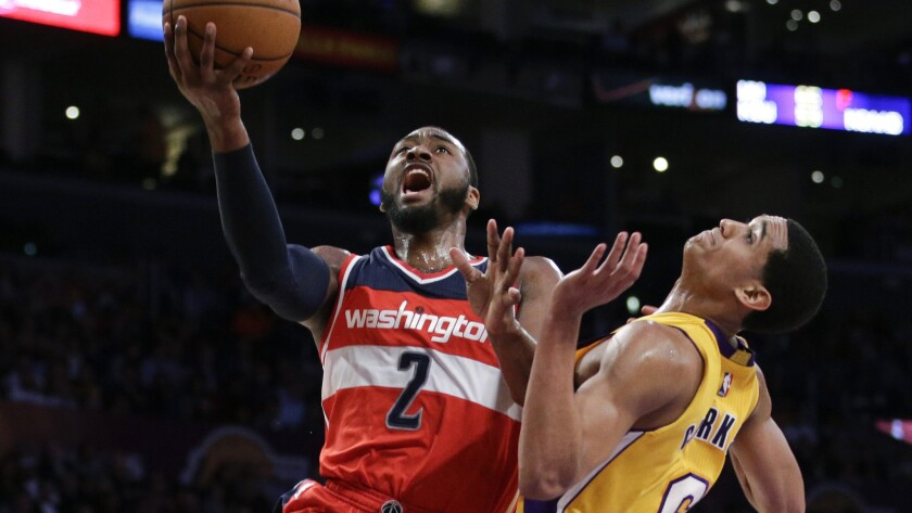 Washington Wizards guard John Wall, left, drives to the basket past Lakers guard Jordan Clarkson during the second half of the Wizards' 98-92 win Tuesday. Wall has played a key role in transforming Washington into one of the Eastern Conference's top teams.