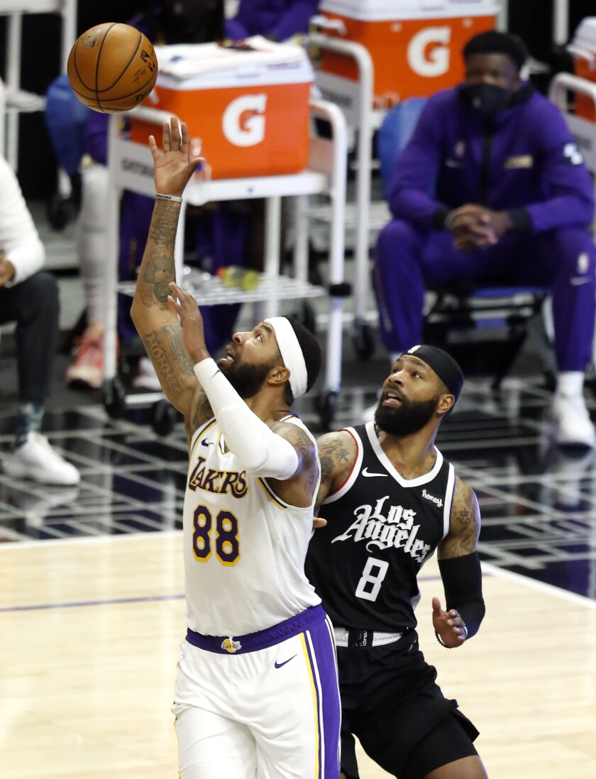 Lakers forward Markieff Morris receives a pass in front of twin brother and Clippers forward Marcus Morris Sr.