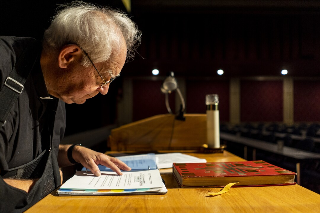 Father Charlie Urnick looks over his notes
