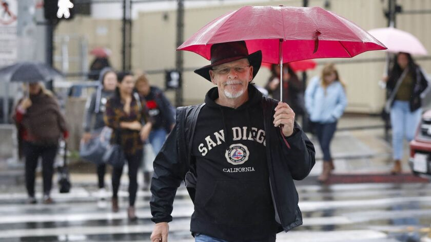 SAN DIEGO, CA 11/29/2018: Tijuana resident Lenny Brisendine, along with others, use umbrellas to sta