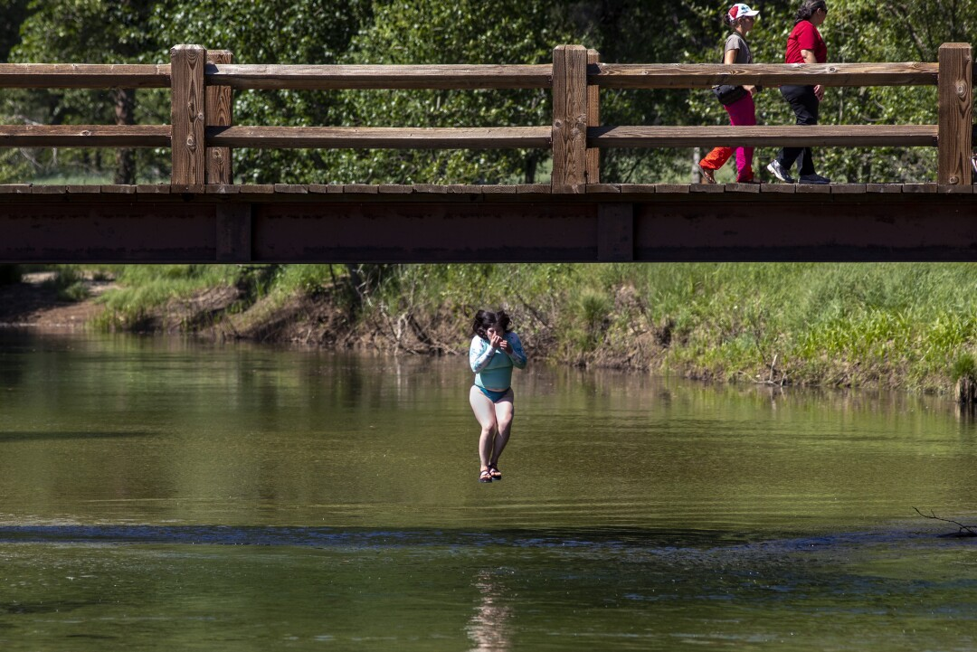 A young woman jumps off Swinging Bridge into the frigid Merced River.