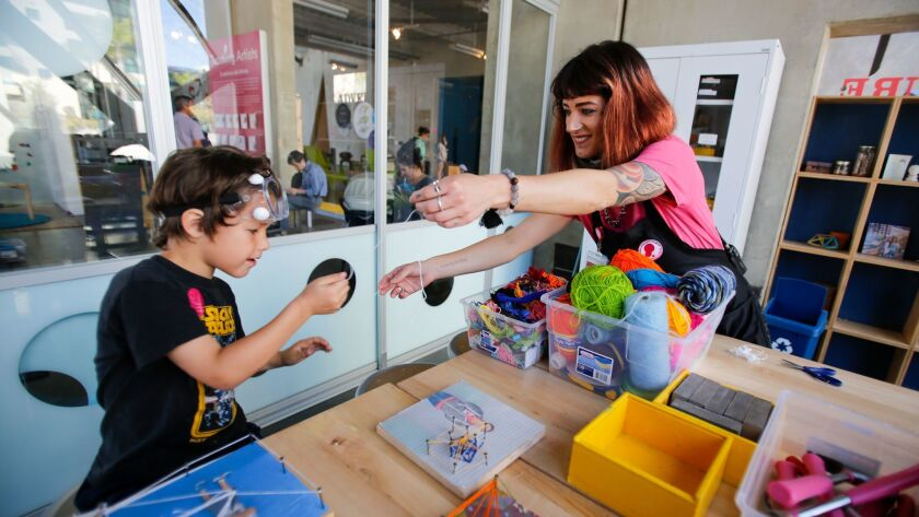 Seven-year-old Jack Economou of Phoenix puts together a design with help from teaching artist Brittany Dumas in the Innovators Lab at the New Children's Museum in downtown San Diego.