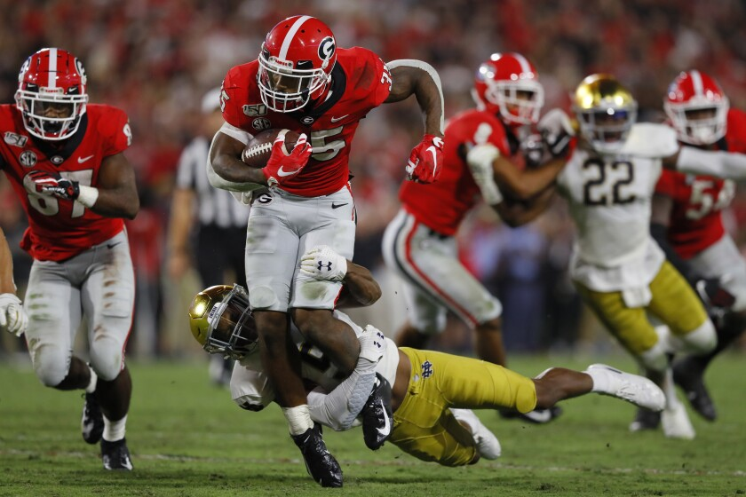 Georgia's Brian Herrien (35) battles for yards against Notre Dame's Troy Pride Jr. (5) during a second half run on Saturday in Athens, Ga.