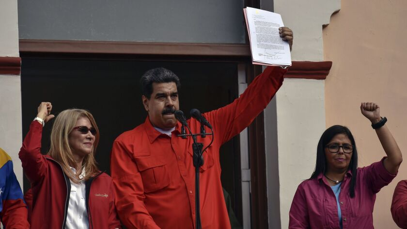 Venezuelan President Nicolas Maduro speaks to a crowd of supporters as he is flanked by his wife, Cilia Flores, left, and Vice President Delcy Rodriguez on Jan. 23, 2019.