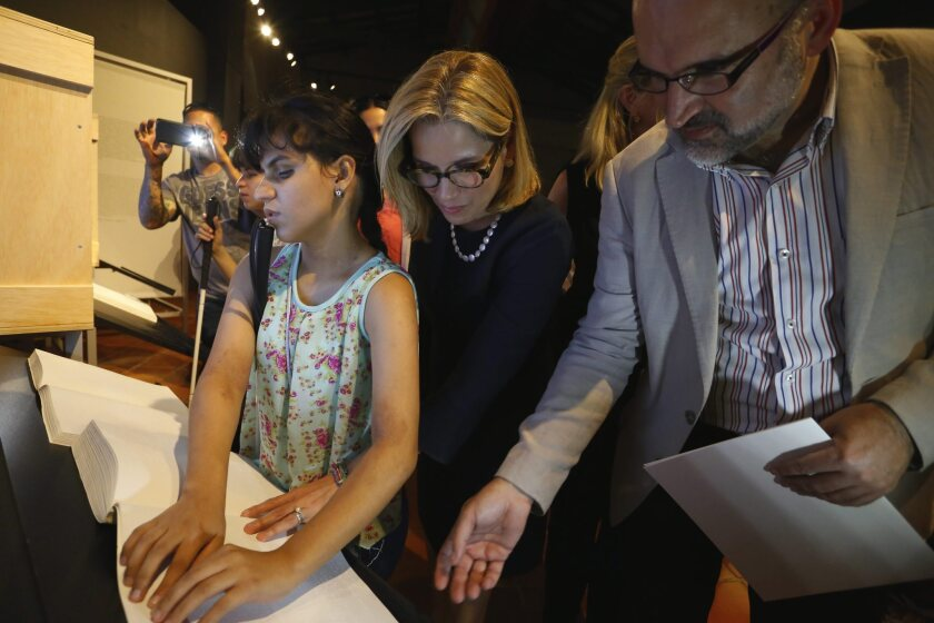 "The mayor of San Juan, center, and José Manuel Lucía of the Spanish Royal Academy observe a woman reading the Spanish master work ""Don Quixote"" in Braille."