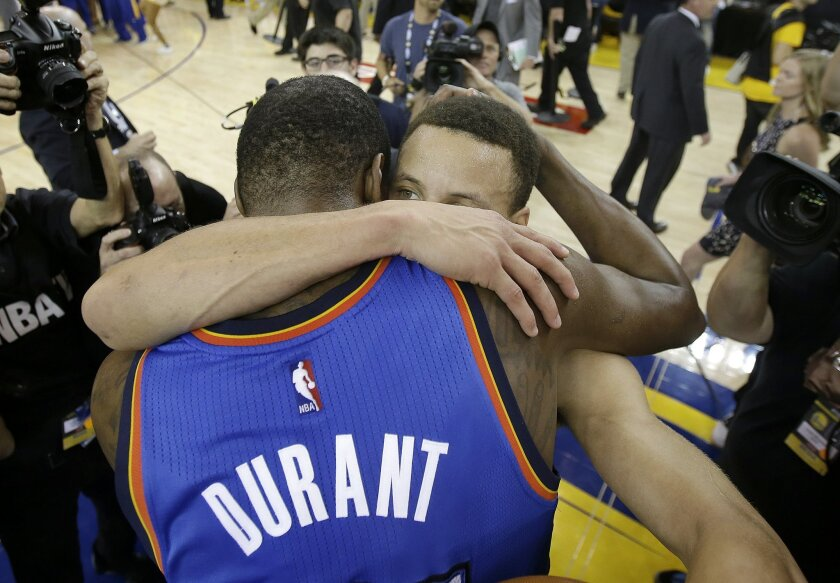 Oklahoma City Thunder forward Kevin Durant, foreground, hugs Golden State Warriors guard Stephen Curry after Game 7 of the NBA basketball Western Conference finals in Oakland, Calif., Monday, May 30, 2016. The Warriors won 96-88. (AP Photo/Marcio Jose Sanchez)