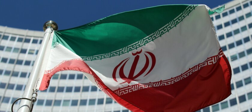 The Iranian flag flies in front of a UN building where closed-door nuclear talks take place at the International Center in Vienna, Austria, Friday, July 4, 2014.