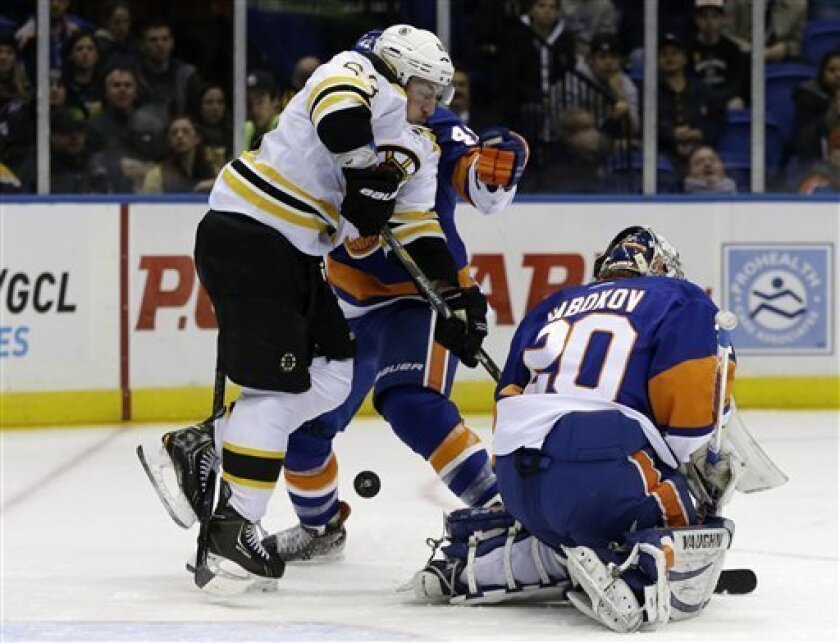 New York Islanders defenseman Andrew MacDonald (47) and goalie Evgeni Nabokov (20) cannot block a shot by Boston Bruins defenseman Adam McQuaid, not shown, as left wing Brad Marchand (63) jumps out of the way in the first period of their NHL hockey game at Nassau Coliseum in Uniondale, N.Y., Tuesda
