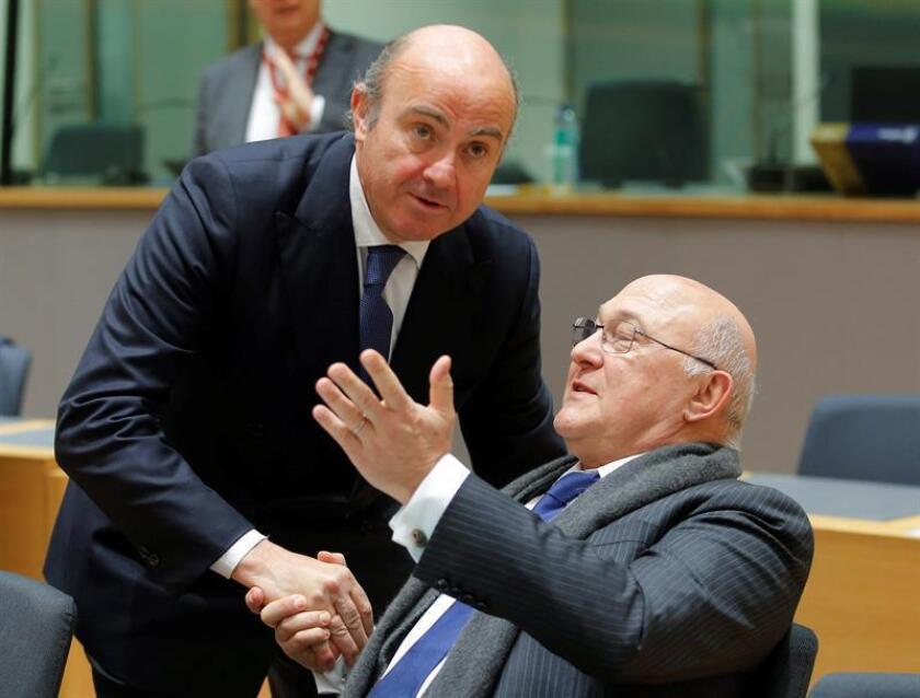 El ministro de Economía español, Luis de Guindos (i), conversa con el ministro de Finanzas francés, Michel Sapin (d), durante la reunión de ministros de Economía y Finanzas de la eurozona (Eurogrupo), hoy en Bruselas. EFE