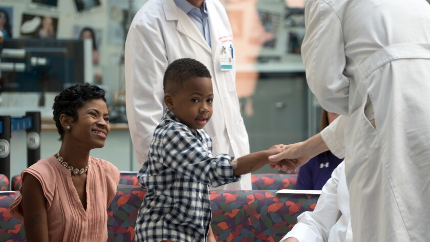 Zion Harvey, al centro, quien recibió un doble trasplante de manos en julio de 2015, saluda de mano a un asistente médico mientras lo observa su madre Pattie Ray, izquierda, durante una conferencia de prensa realizada el martes 23 de agosto de 2016 en el Hospital Infantil de Filadelfia. (AP Foto/Dake Kang)