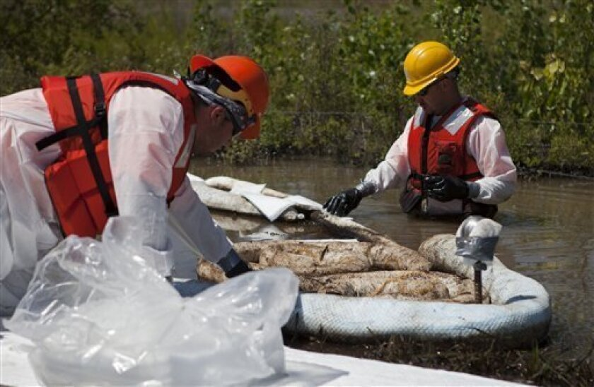 Cleanup workers use oil absorbent materials along side the Yellowstone River in Laurel, Montana, Wednesday July 6, 2011. An Exxon Mobil pipeline near Laurel, Montana ruptured and spilled an estimated 1,000 barrels of crude into the Yellowstone. (AP Photo/Jim Urquhart)