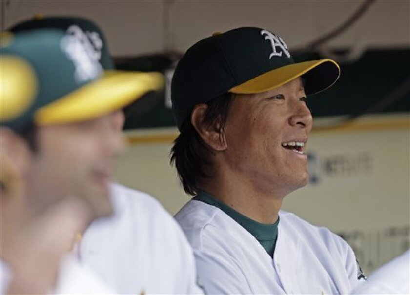 Oakland Athletics' Hideki Matsui, right, of Japan, smiles in the dugout prior to the baseball game against the Seattle Mariners Friday, April 1, 2011, in Oakland, Calif. (AP Photo/Ben Margot)